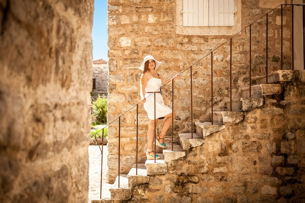 Schöne elegante frau, die auf steintreppen an der alten straße steht