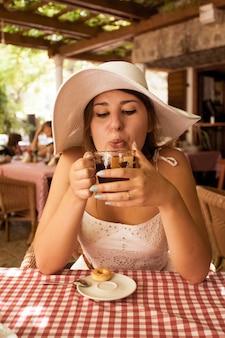 Schöne elegante frau, die heißen tee zum frühstück im café trinkt