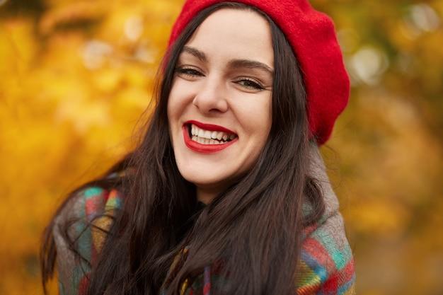 Schöne elegante frau, die im herbst im park steht, junge frau mit charmantem lächeln, das rote baskenmütze und gewickelte warme karierte decke trägt