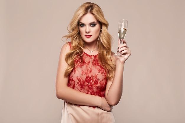 Schöne elegante frau im modernen kleid mit glas champagner