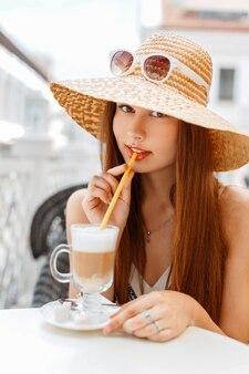 Schöne elegante frau in einem hut und in der sonnenbrille, die einen köstlichen latte in einem sommercafé trinken.