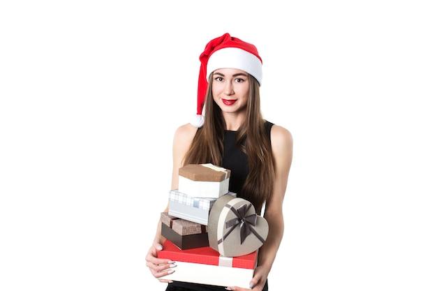 Schöne elegante frau in einem schwarzen kleid mit geschenken, die auf einem weißen hintergrund lächeln. überraschung für den urlaub.