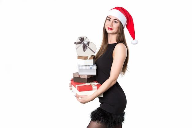 Schöne elegante frau in einem schwarzen kleid und weihnachtsmütze mit geschenken lächelt auf einem weißen hintergrund. überraschung für den urlaub.