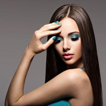 Schöne elegante frau mit türkisfarbenem make-up und nägeln - pose