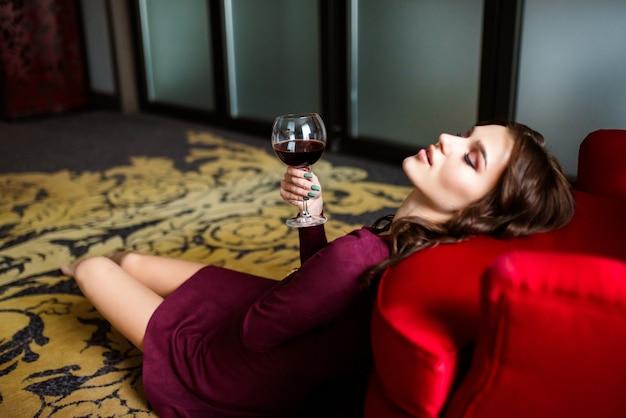 Schöne elegante frau sitzt auf einem sessel und trinkt ein glas wein