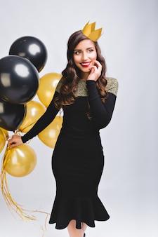 Schöne elegante junge frau im modekleid feiert neujahrsparty und hält goldene und schwarze luftballons. hat langes brünettes haar, gelbe krone. spaß haben, magische nacht, geburtstag.