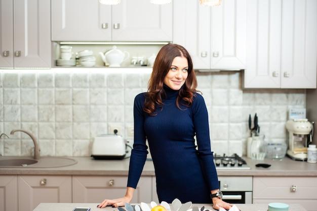 Schöne elegante lächelnde frau, die in der küche mit obst kocht