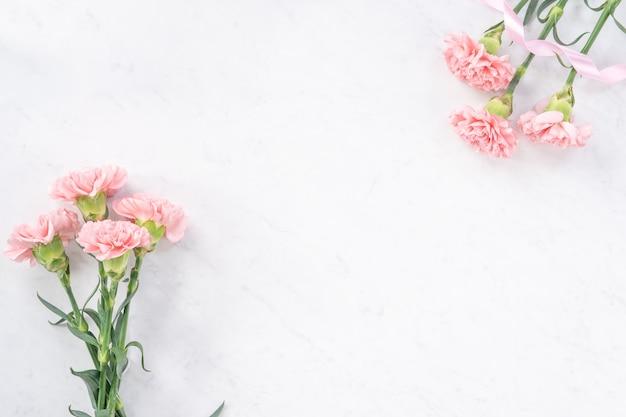 Schöne, elegante rosa nelkenblume über hellweißem marmortisch