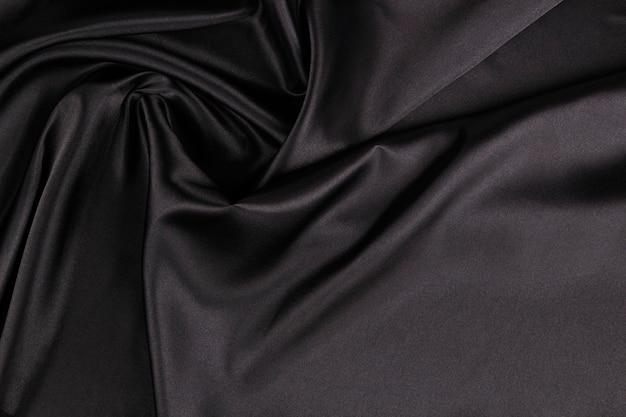 Schöne elegante schwarze wand mit vorhängen und gewellten falten aus seidensatinmaterial. draufsicht