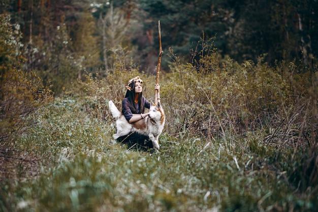 Schöne elfenfrau, feenhafter wald, goldene kranzkrone des langen dunklen haares auf kopf mit rotem hund