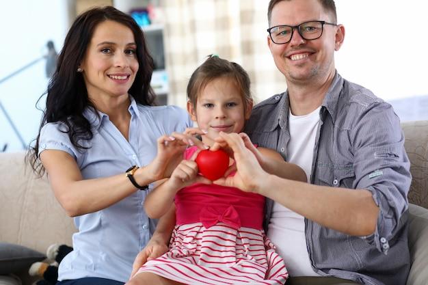 Schöne eltern und kleines kind halten rotes herz zusammen.