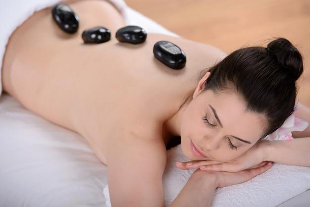 Schöne entspannende frau mit steinen auf dem rücken in einem spa