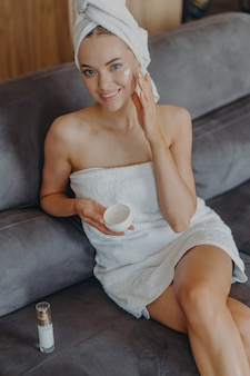 Schöne entspannte frau eingewickelt im handtuch, das tee trinkt