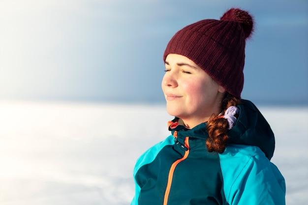 Schöne entspannte junge frau, die kaltes sonniges winterwetter genießt