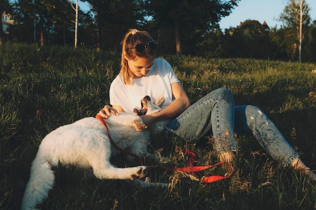 Schöne entspannte junge frau in der leichten freizeitkleidung, die auf grünem gras liegt und umarmt und spielt mit dem auf dem rücken liegenden glücklichen weißen hund mit offenen kiefern bei sonnenuntergang