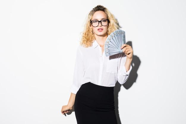 Schöne erfolgsgeschäftsfrau, die dollarnoten hält, lokalisiert auf weißer wand