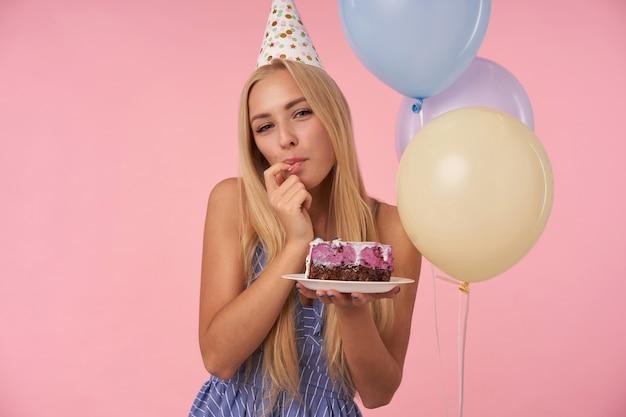 Schöne erfreute langhaarige frau im blauen sommerkleid und im feiertagskegelhut, der leckeren kuchen über rosa hintergrund schmeckt, ihren zeigefinger leckt und kamera mit glücklichem lächeln betrachtet