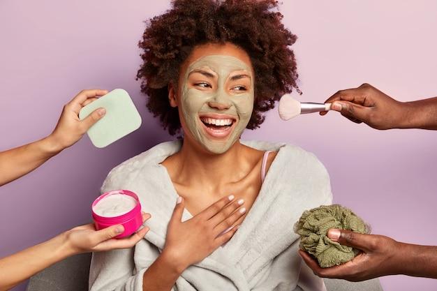 Schöne erfrischte fröhliche frau mit pflegender tonmaske schaut glücklich beiseite, behandelt mit creme, schwämmen und make-up-pinsel