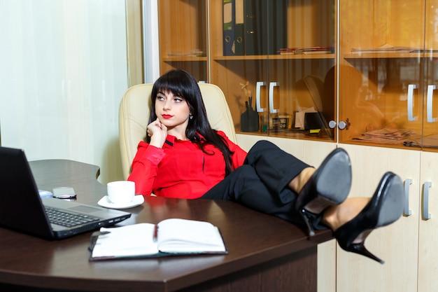 Schöne ernste frau, die am tisch in einem büro sitzt
