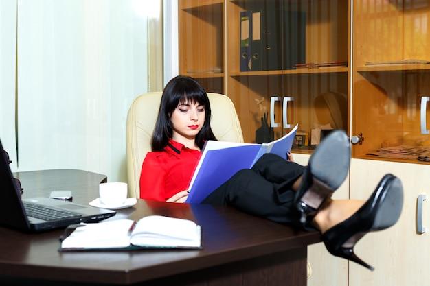 Schöne ernste frau, die dokumente am tisch in einem büro liest