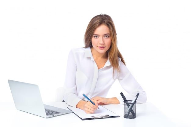 Schöne ernste junge geschäftsfrau, die am tisch lokalisiert über weißem hintergrund sitzt