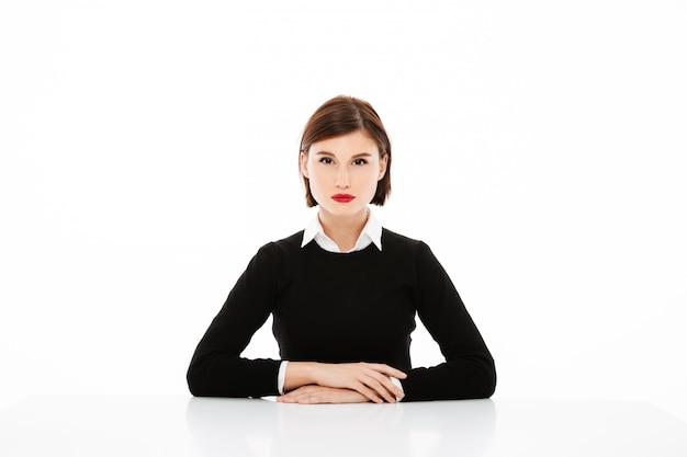 Schöne ernste junge geschäftsfrau, die am tisch, vorstellungsgesprächkonzept sitzt