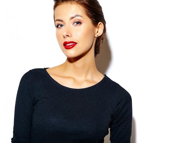 Schöne ernste nette reizvolle brunettefrau im beiläufigen schwarzen kleid mit den roten lippen auf weißer wand