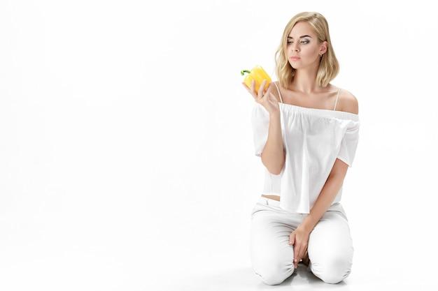 Schöne ernsthafte blonde frau in einer weißen bluse schaut auf die gelbe paprika. gesunde ernährung und ernährung