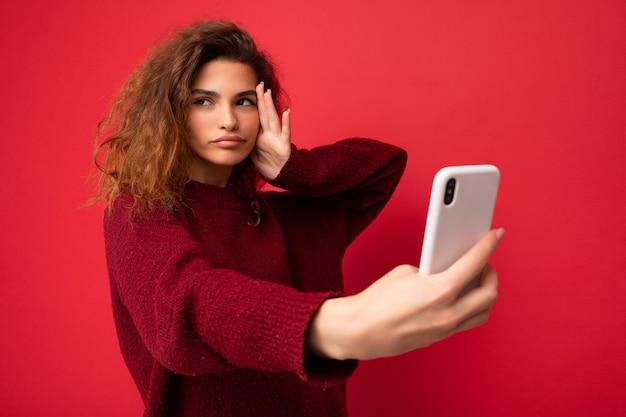 Schöne ernsthafte konzentrierte junge frau mit dem lockigen haar, das dunkelroten pullover lokalisiert auf rotem hintergrundwand hält, der smartphone hält und verwendet, das zur seite schaut und selfie nimmt.