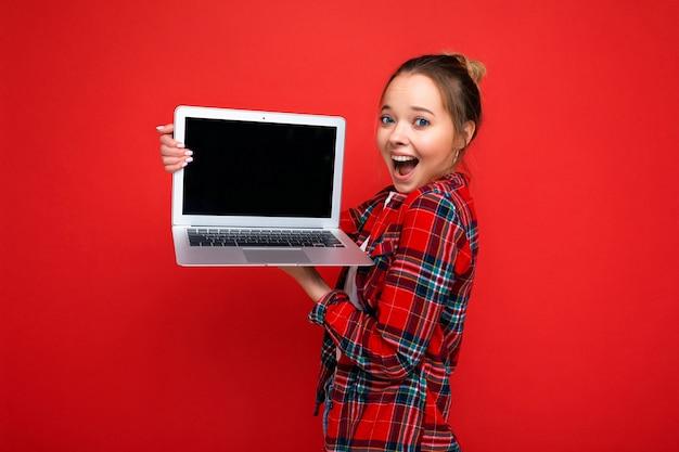 Schöne erstaunte junge frau mit laptop mit rotem hemd und blick in die kamera auf rotem hintergrund