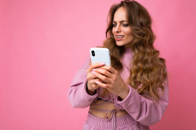 Schöne erstaunte überraschte blonde junge frau mit rosafarbenem hoodie einzeln auf rosafarbenem hintergrund mit kopienraum, der das handy hält und auf die geräteanzeige schaut.