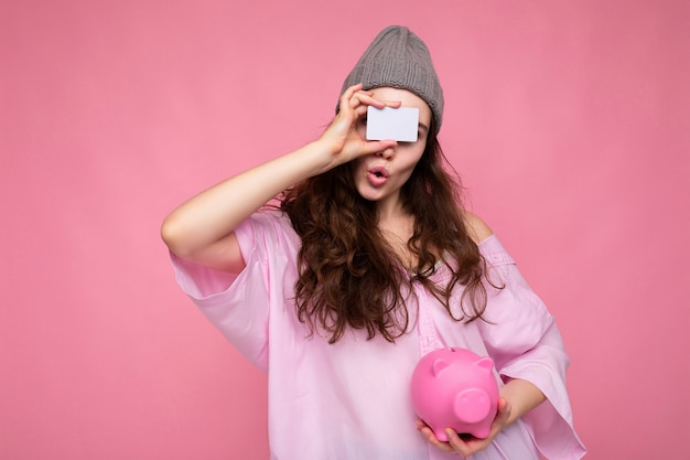 Schöne erstaunte überraschte junge brünette frau mit hemd isoliert auf rosa hintergrund mit freiem