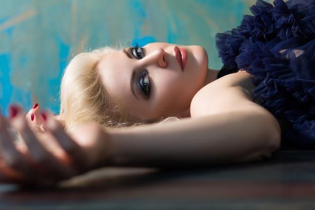 Schöne erwachsene blonde frau, die auf boden legt. schauspielerin spielt rolle auf der bühne.