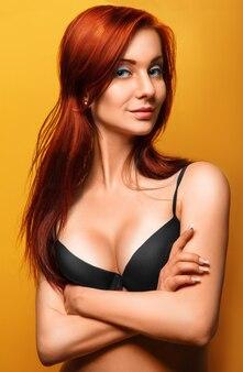 Schöne erwachsene frau des roten haares im schwarzen bh auf gelb