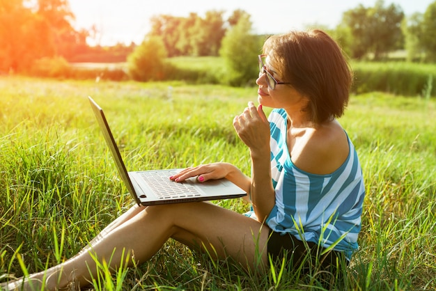Schöne erwachsene frau, die auf laptop schreibt