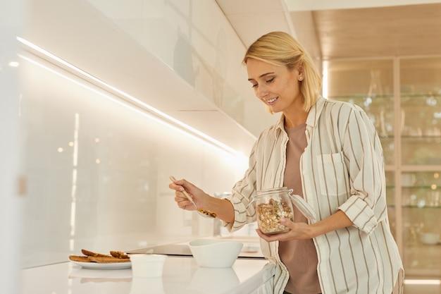 Schöne erwachsene frau, die gesundes frühstück macht, während sie im glamourösen kücheninnenraum steht