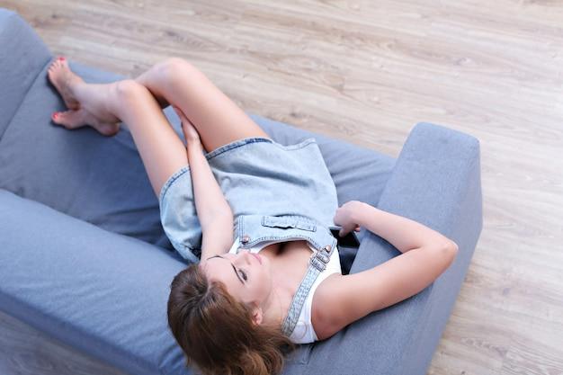 Schöne erwachsene frau, die in der couch liegt