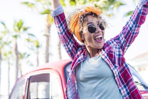 Schöne erwachsene frau jubelt aufgeregt im freien mit rotem auto und palmen im hintergrund - sommerurlaubsreise-lifestyle mit fröhlichen weiblichen menschen - feierzeit eine person