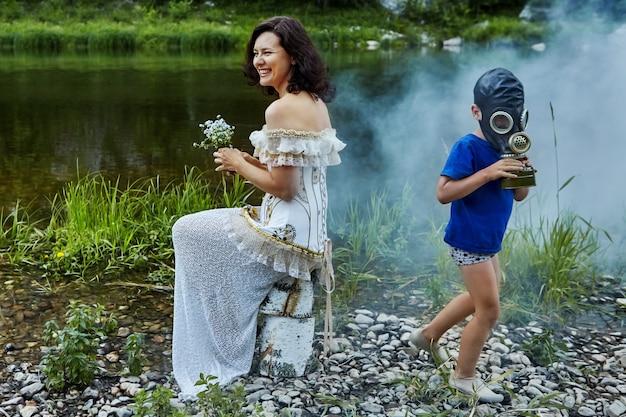 Schöne erwachsene frau lacht, sitzt am flussufer mit einem strauß wildblumen in ihren händen, trägt hochzeits- oder abendkleid, und kind in der schützenden gasmaske läuft in der nähe.