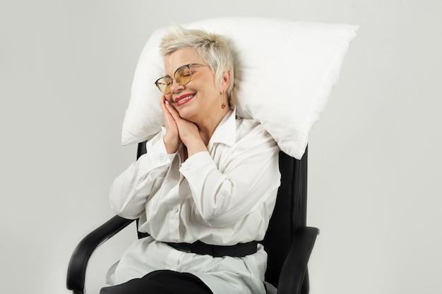Schöne erwachsene frau mit brille schläft in einem stuhl mit einem kissen