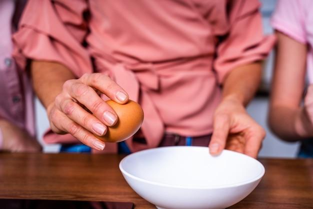 Schöne erwachsene frau und tochter backen in der küche