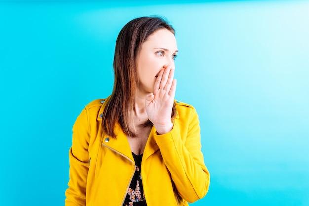 Schöne erwachsene junge frau in gelber jacke, die mit der hand auf dem mund ein geheimnis erzählt. geflüstertes geheimes konzept
