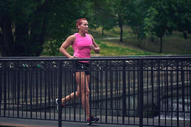 Schöne erwachsene rothaarige sportlerin in der rosa spitze und in den kurzen hosen lässt den morgen auf der stadtbrücke über dem fluss laufen. gesunder lebensstil, joggen