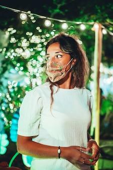 Schöne europäische frau, die eine blumenmaske an einem vergnügungspark trägt