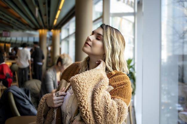 Schöne europäische frau, die einen modischen orangefarbenen mantel trägt und ihre zeit in einem café genießt