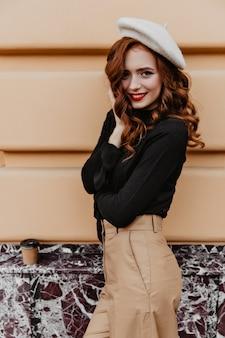 Schöne europäische frau in der braunen baskenmütze, die guten tag genießt. wunderbares französisches weibliches modell mit ingwerhaar, das draußen aufwirft.
