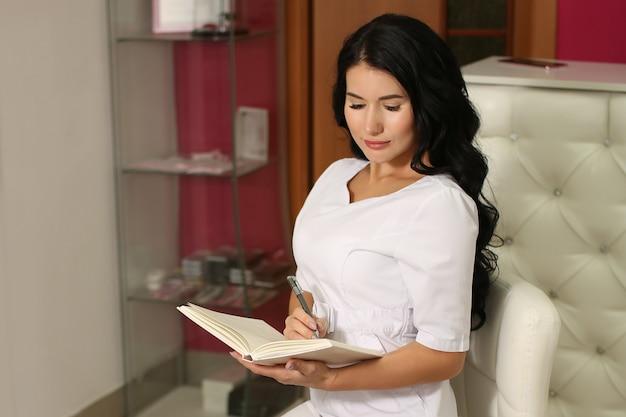 Schöne europäische frau schreibt informationen in ein notizbuch in weißen kleidern in einer uniform. der geschäftsinhaber sitzt in einem schönheitssalonbüro.