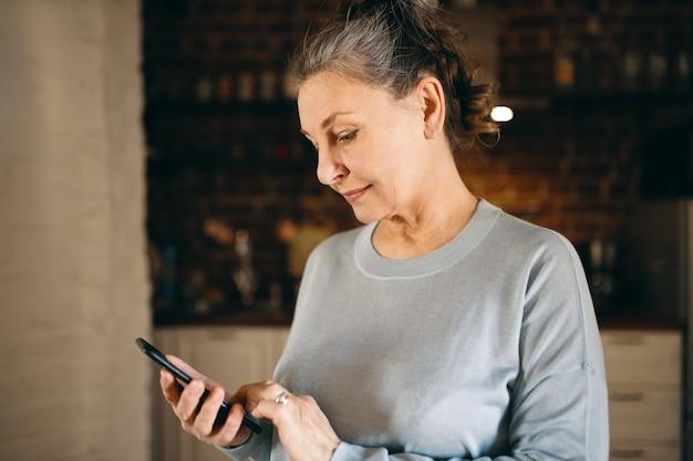 Schöne europäische großmutter hält handy, sms an ihren sohn, surft in sozialen netzwerken, sieht bilder, chattet online zu hause