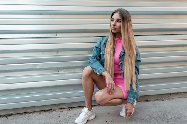 Schöne europäische junge blonde frau in einer blauen jeansjacke in trendigen rosa shorts in einem rosa oberteil in stilvollen weißen turnschuhen sitzt in der nähe einer metallwand auf einer straße an einem sommertag. nettes mädchen wirft draußen auf