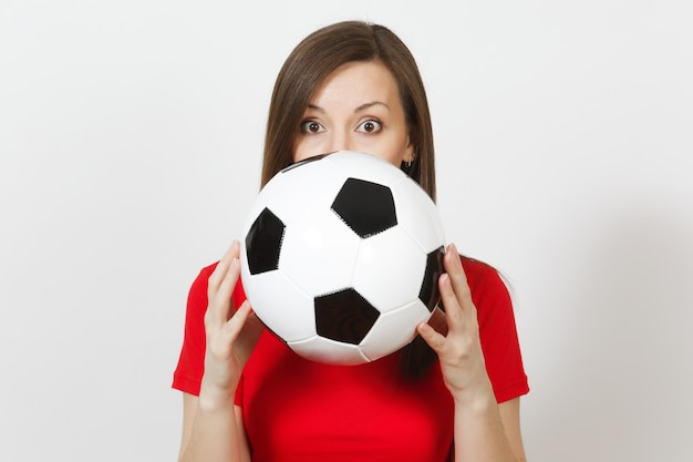 Schöne europäische junge frau, fußballfan oder spieler in der roten uniform, die sich hinter dem klassischen fußball verbirgt, der auf weißem hintergrund lokalisiert wird. sport, fußball spielen, gesundheit, gesundes lebensstilkonzept.